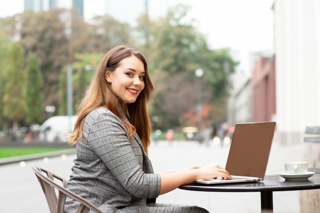 Geschäftsfrau, die in einer kaffeestube auf der straße, arbeitend an einem laptop sitzt. Premium Fotos