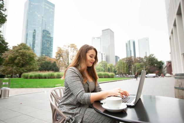 Geschäftsfrau, die in einer kaffeestube auf der straße in der stadt, arbeitend an einem laptop sitzt. Premium Fotos