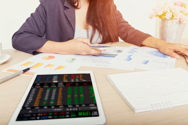 Geschäftsfrau, die investitionsdiagramme mit digitalen daten auf mobile und tablette analysiert Premium Fotos