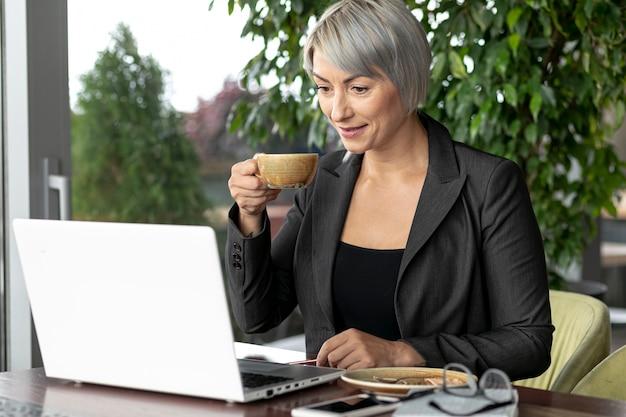 Geschäftsfrau, die kaffee beim arbeiten trinkt Kostenlose Fotos