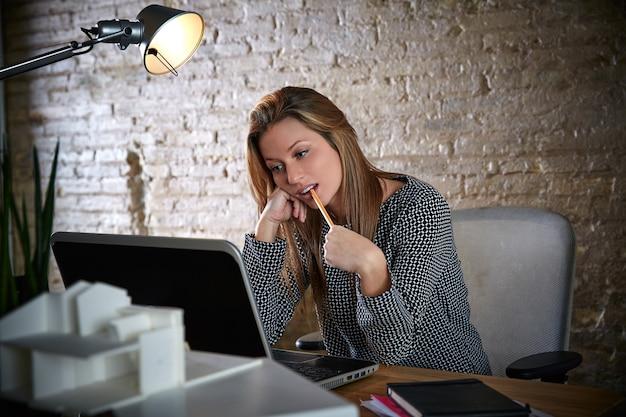 Geschäftsfrau, die mit bleistift im mund denkt Premium Fotos
