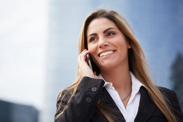 Geschäftsfrau, die mit mobile in der städtischen umwelt spricht Premium Fotos