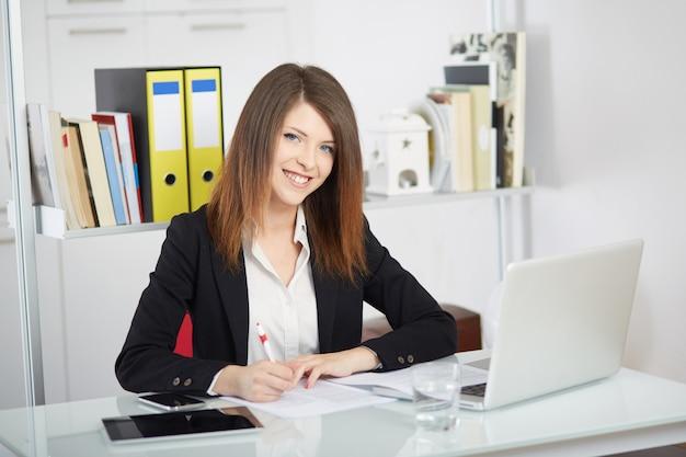 Geschäftsfrau, die mit mobile spricht und im büro mit laptop arbeitet Premium Fotos