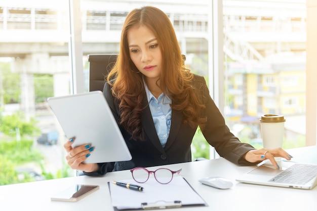 Geschäftsfrau, die mobile mit laptop auf schreibtisch im büro verwendet. Premium Fotos