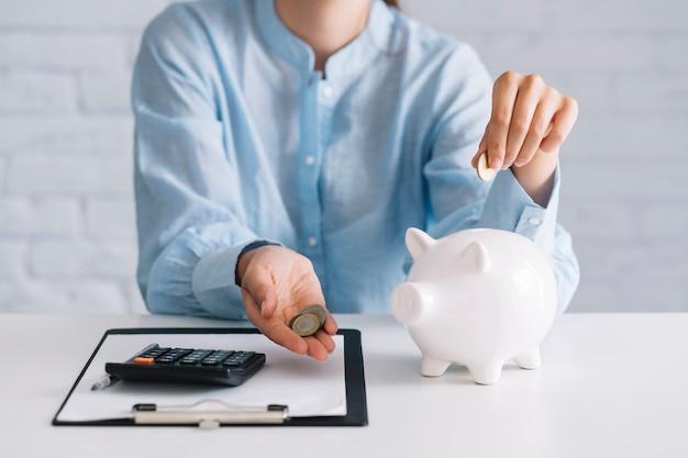Geschäftsfrau, die münzen mit weißem piggybank auf schreibtisch zeigt Kostenlose Fotos