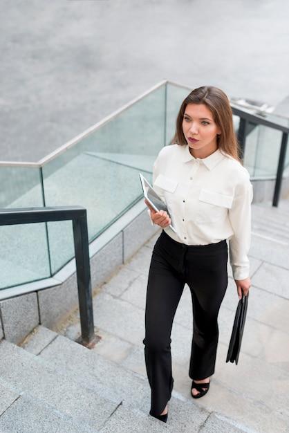 Geschäftsfrau, die oben die treppe klettert Kostenlose Fotos