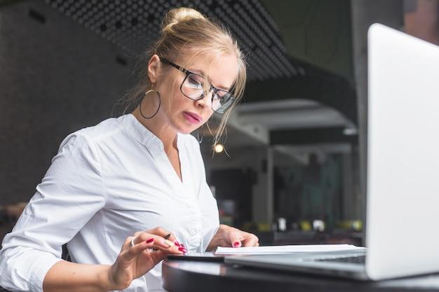 Geschäftsfrau, die smartphone bei der herstellung von anmerkungen verwendet Kostenlose Fotos