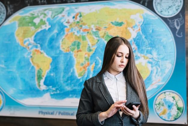 Geschäftsfrau, die smartphone im büro verwendet Kostenlose Fotos