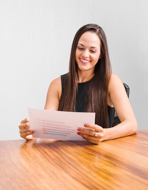 Geschäftsfrau, die über statistiken glücklich ist Kostenlose Fotos
