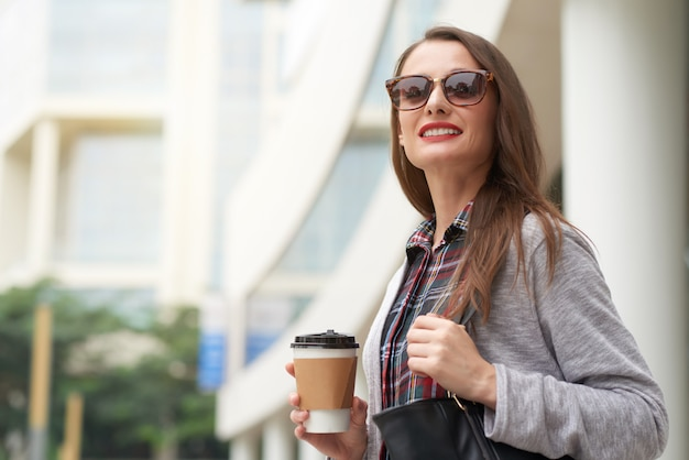 Geschäftsfrau, die weg vorangeht, um mit mitnehmerkaffee morgens zu arbeiten Kostenlose Fotos