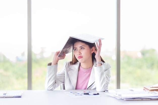 Geschäftsfrau gelangweilt von der arbeit mit vielem dokument und arbeit im laptop im büro Premium Fotos