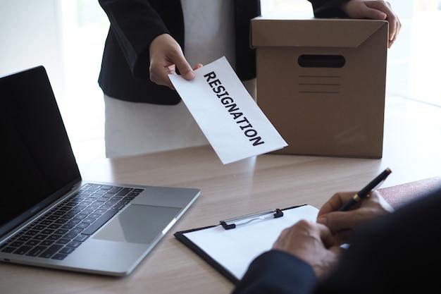 Geschäftsfrau haben boxen für den persönlichen gebrauch und senden kündigungsschreiben an führungskräfte Premium Fotos
