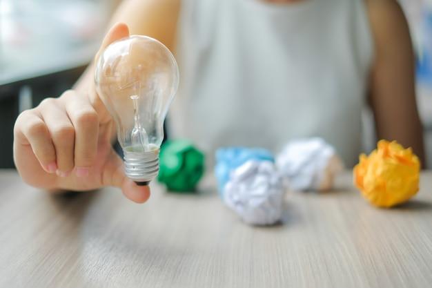 Geschäftsfrau hand, die glühlampe oder lampe mit buntem zerknittertem papier hält Premium Fotos