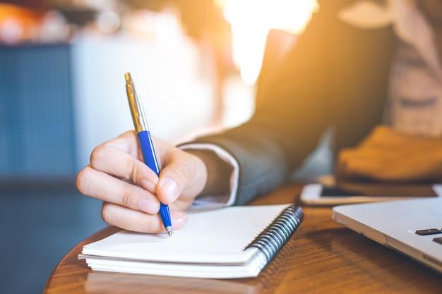 Geschäftsfrau-handschrift auf notizblock mit einem stift im büro. Premium Fotos