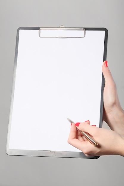 Geschäftsfrau holding a clipboard and writing Premium Fotos