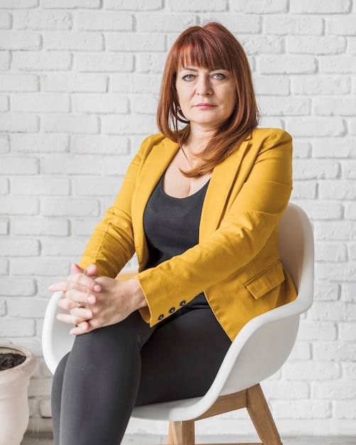 Geschäftsfrau im büro, das auf stuhl sitzt Kostenlose Fotos