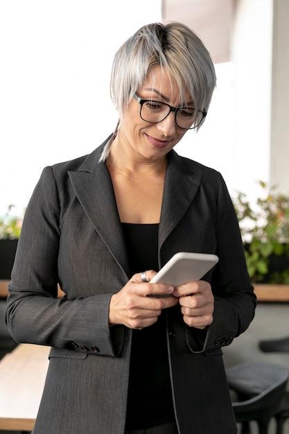 Geschäftsfrau im büro mobile überprüfend Kostenlose Fotos
