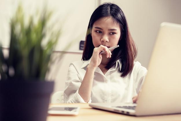 Geschäftsfrau im büro und benutzen computer, um finanzbuchhaltung durchzuführen. Premium Fotos