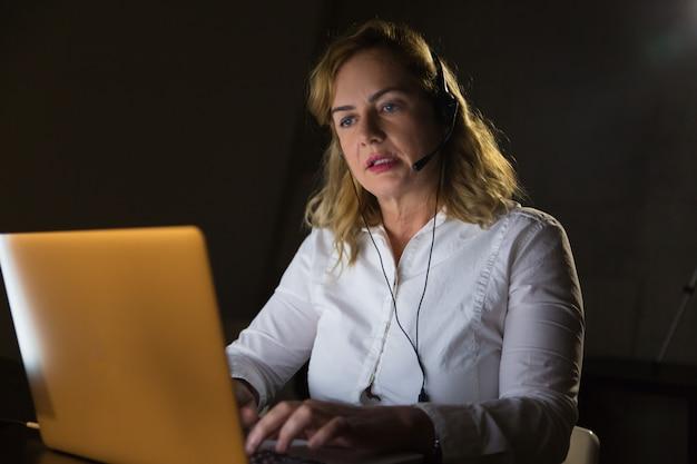 Geschäftsfrau im kopfhörer unter verwendung der laptop-computers Kostenlose Fotos