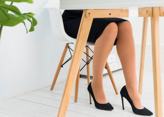 Geschäftsfrau im rock, der bei tisch im büro sitzt Kostenlose Fotos