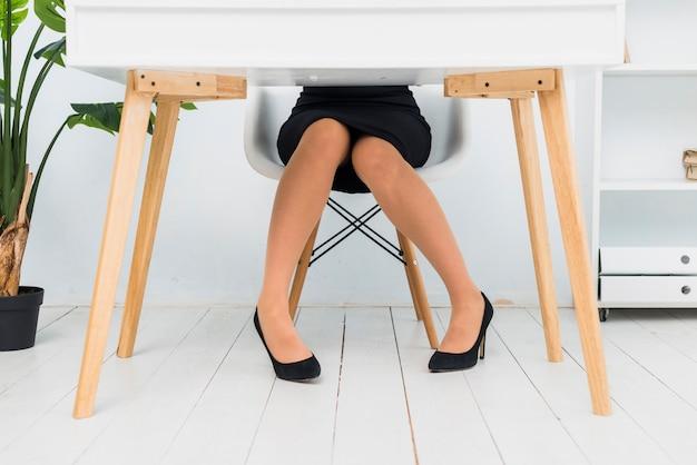 Geschäftsfrau im rock und in schuhen, die am tisch sitzen Kostenlose Fotos