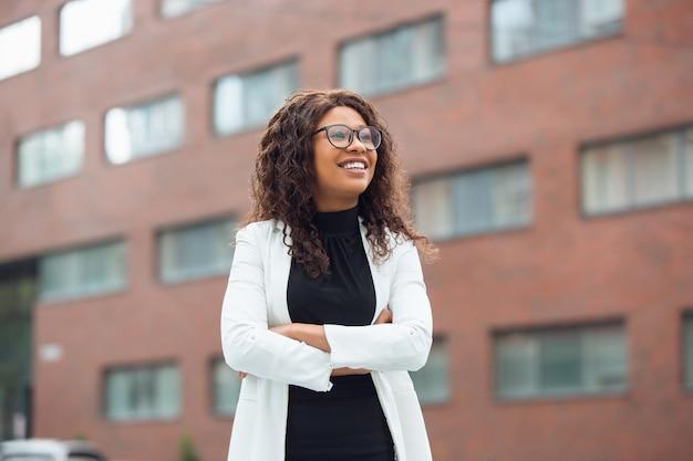 Geschäftsfrau in bürokleidung lächelt, sieht selbstbewusst und glücklich aus Kostenlose Fotos