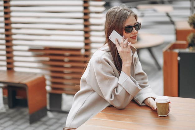 Geschäftsfrau in einem café trinkendes coffe, unter verwendung des telefons Kostenlose Fotos