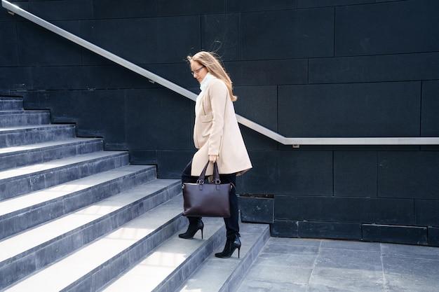 Geschäftsfrau in einem mantel mit einer tasche in den händen geht die stufen zum gebäude hinauf. Kostenlose Fotos
