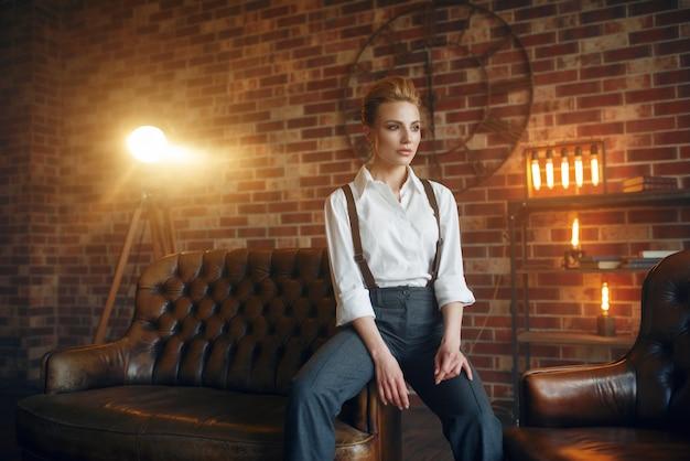 Geschäftsfrau in strengen kleidern auf ledercouch Premium Fotos