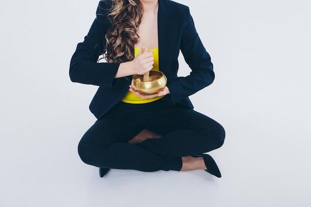 Geschäftsfrau meditieren. vorbereitung eines tranks auf einem weiß. klangschale mit buddhistischem mantra in frauenhand in anzug Premium Fotos