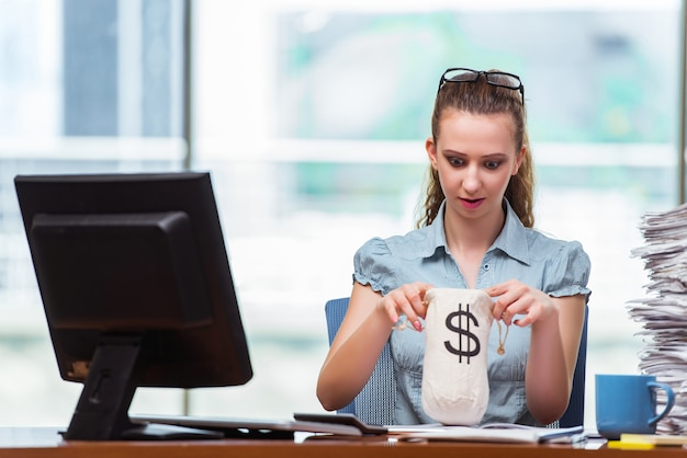 Geschäftsfrau mit geldsäcken im büro Premium Fotos