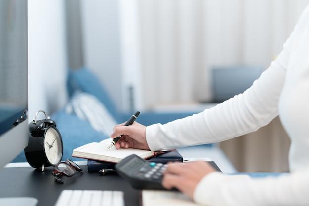 Geschäftsfrauen arbeiten mit taschenrechner- und computerdesktop auf moderner arbeitstabelle Premium Fotos