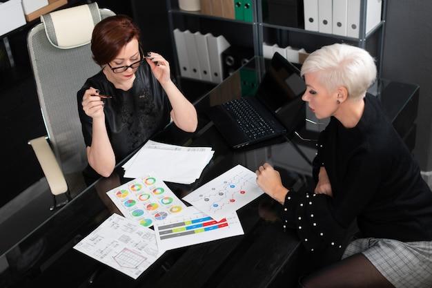 Geschäftsfrauen besprechen diagramme am schreibtisch im büro Premium Fotos