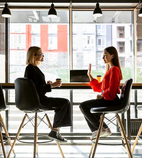 Geschäftsfrauen, die bei der arbeit gebärdensprache verwenden, um miteinander zu sprechen Kostenlose Fotos
