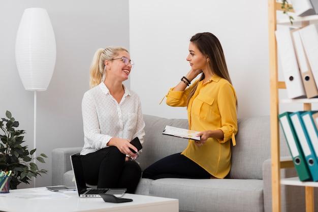 Geschäftsfrauen, die ein telefon und ein klemmbrett anhalten Kostenlose Fotos