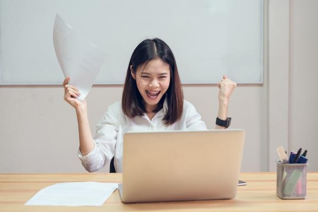 Geschäftsfrauen sind glücklich, in der arbeit erfolgreich zu sein, und zeigen dokument auf dem tisch im office zurück Premium Fotos