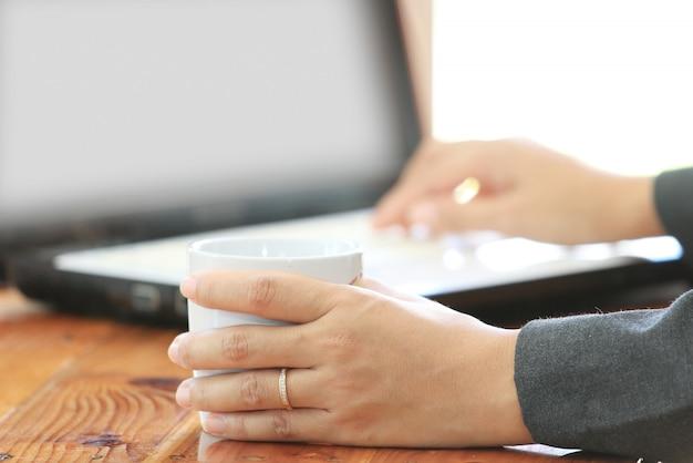 Geschäftsfraugriff eine kaffeetasse und anwendung der laptop-computers Premium Fotos