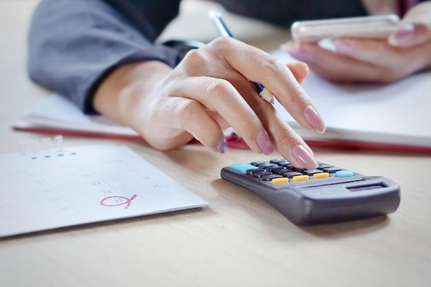 Geschäftsfrauhand, die ihre monatlichen ausgaben während der steuerjahreszeit berechnet Premium Fotos