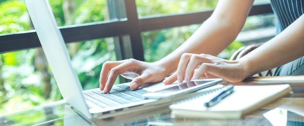 Geschäftsfrauhand, die mit einer laptop-computer im büro arbeitet. Premium Fotos