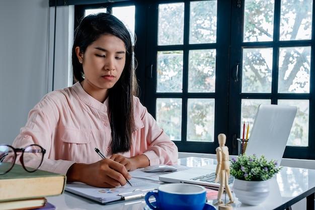 Geschäftsfrauhand, die mit finanzdaten und taschenrechner auf weißem schreibtisch herein modern weg arbeitet Premium Fotos