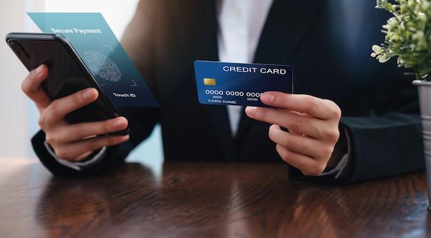 Geschäftsfrauhand, die sichere zahlung der kreditkarte und der smartphoneschnittstelle hält. Premium Fotos