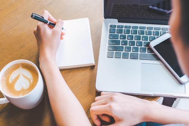 Geschäftsfrauhand schreibt auf einen notizblock mit einem stift. Premium Fotos