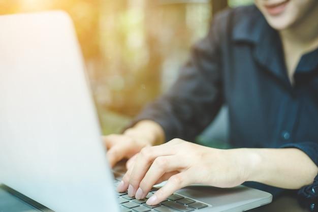 Geschäftsfrauhandarbeitslaptop-computer im büro Premium Fotos
