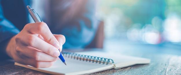 Geschäftsfrauhandschrift auf einem notizblock mit einem stift im büro. Premium Fotos