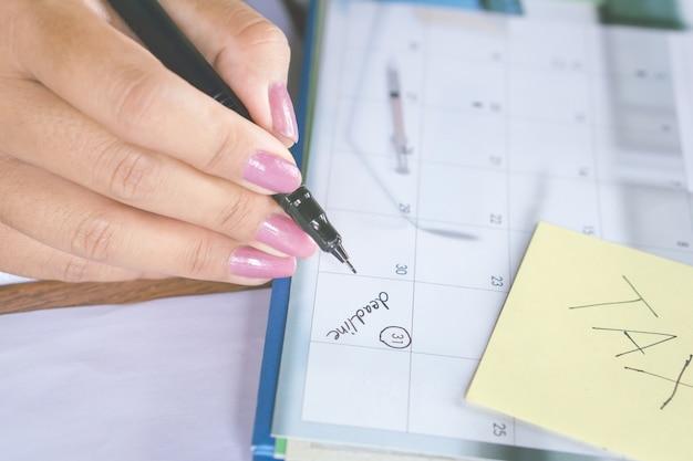 Geschäftsfrauhandschrift auf kalenderabschlußwort für steuerzeit Premium Fotos