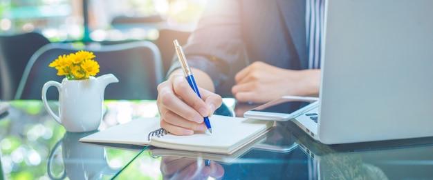 Geschäftsfrauschreiben auf einem notebookwith einem stift im büro Premium Fotos