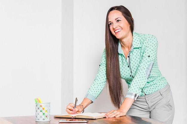 Geschäftsfrauschreiben auf ihrem notizbuch Kostenlose Fotos
