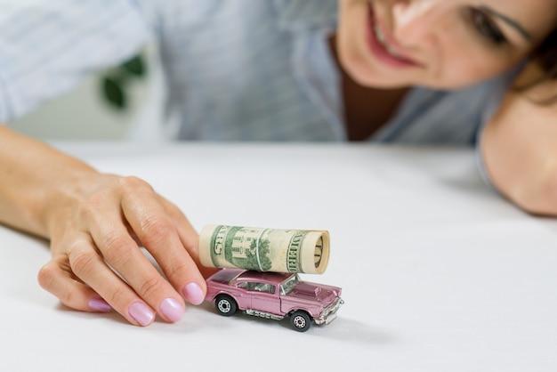Geschäftsfrauspielzeugauto und -geld - zielen des erfolgs und des glückes Premium Fotos