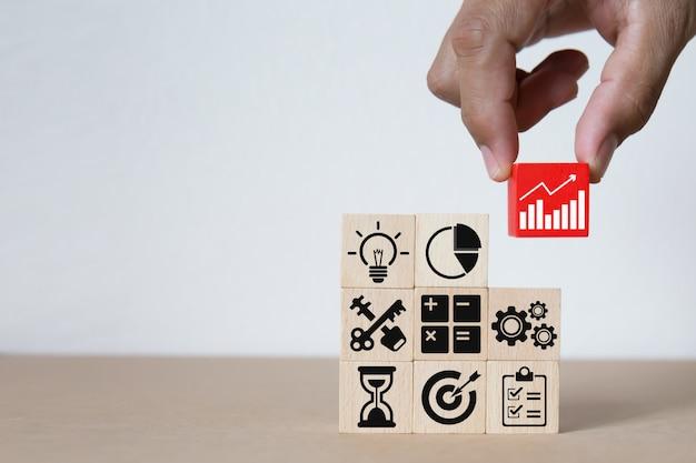 Geschäftsgrafik-ikonen auf holzklötzen. Premium Fotos