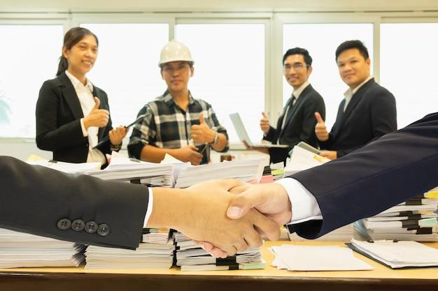 Geschäftshändedruck erfolgreich mit stapel der schreibarbeit und gruppe teamwork im hintergrund. Premium Fotos